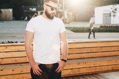 Front view. Young bearded hipster man dressed in white t-shirt and sunglasses is stands on city street. Mock up. Summer day. Front view. Young bearded hipster Stock Images