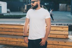 Front view. Young bearded hipster man dressed in white t-shirt and sunglasses is stands on city street. Mock up. Royalty Free Stock Image