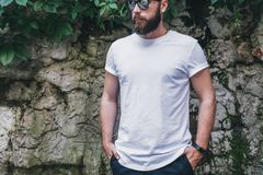 Front view. Young bearded millennial man dressed in white t-shirt and sunglasses is stands against dark wall. Mock up. Summer day. Front view. Young bearded stock photos
