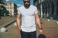Front view. Young bearded millennial man dressed in white t-shirt and sunglasses is stands on city street. Mock up. Summer day. Front view. Young bearded Royalty Free Stock Photography