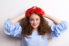 A front view of young beautiful woman with flower headband, hands behind head. royalty free stock photos