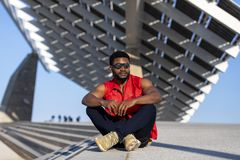 Front view of a young black man wearing sunglasses sitting on staircase in a sunny day while looking away royalty free stock images