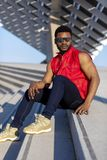 Front view of a young black man wearing sunglasses sitting on staircase in a sunny day while looking camera stock photo
