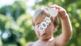 Front view of a young blond child blowing soap bubbles royalty free stock photos