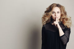 Front view of young blonde woman with curly hair holding finger on lips and gesturing sign of silence. Posing at camera. Wearing i Stock Image