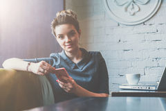Front view of young business woman sitting in cafe at table and holding smartphone while looking at camera. On table laptop and cup of coffee. On background Royalty Free Stock Photography