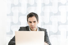 Front view of a young businessman in a high key office typing in Stock Photo