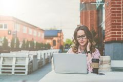 Front view.Young businesswoman with glasses is sitting at table in street cafe and uses laptop. Royalty Free Stock Images