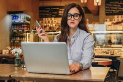 Front view. Young businesswoman is sitting in cafe working on laptop. Girl blogging, learning online, checking email. Stock Photography
