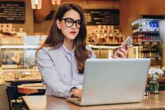 Front view. Young businesswoman is sitting in cafe working on laptop. Girl blogging, learning online, checking email. Royalty Free Stock Photo