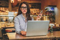 Front view. Young businesswoman is sitting in cafe working on laptop. Girl blogging, learning online, checking email. Royalty Free Stock Image