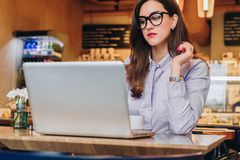 Front view. Young businesswoman is sitting in cafe working on laptop. Girl blogging, learning online, checking email. Royalty Free Stock Photography