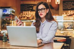 Front view. Young businesswoman is sitting in cafe working on laptop. Girl blogging, learning online, checking email. Stock Photos