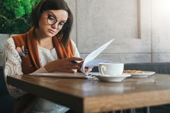 Front view.Young businesswoman is sitting in coffee shop at table,reading documents.Student is studying online. Doing homework.On table cup of tea, cookies. E Royalty Free Stock Photos