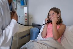 Girl patient listening to doctors heart beat with stethoscope. Front view of young Caucasian patient listening to mixed race female doctors heart beat with stock photo