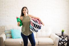 Beautiful young woman is holding a fabric softener and laundry b. Front view of a young cheerful housewife holding basket with dirty clothes for wash and Royalty Free Stock Images