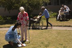 Young female doctor examining disabled senior woman in garden stock photo