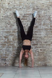 Front view of young fit female athlete doing handstand exercise against brick wall.  Royalty Free Stock Photos