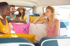 Group of friends having fun in a camper van at beach. Front view of young group of diverse friends having fun in a camper van at beach stock photography