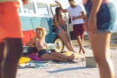 Group of friends having fun near camper van at beach. Front view of young group of diverse friends having fun near camper van at beach stock photography