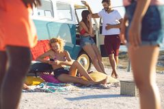 Group of friends having fun near camper van at beach. Front view of young group of diverse friends having fun near camper van at beach royalty free stock photography