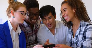 Happy multi-ethnic business colleagues using mobile phone in modern office 4k. Front view of young happy multi-ethnic business colleagues using mobile phone in stock video footage