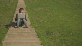 Front View of Young Man Sitting On The Stairs In Park Using Laptop. Outdoors, 4K, UHD stock video