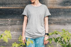 Front view. Young millennial woman dressed in gray t-shirt is stands against gray wood wall. Summer day. Front view. Young millennial woman dressed in gray t Royalty Free Stock Images