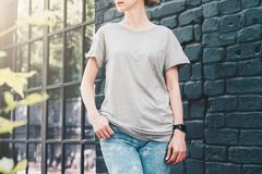 Front view. Young millennial woman dressed in gray t-shirt is stands against gray wood wall. Summer day. Front view. Young millennial woman dressed in gray t Stock Images