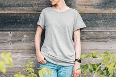Front view. Young millennial woman dressed in gray t-shirt is stands against gray wood wall. Summer day. Front view. Young millennial woman dressed in gray t Royalty Free Stock Photos