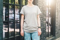 Front view. Young millennial woman dressed in gray t-shirt is stands on city street. Mock up. Summer day. Front view. Young millennial woman dressed in gray t Royalty Free Stock Photo