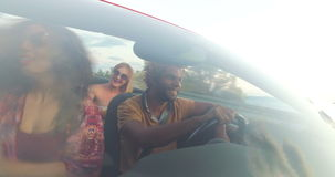 Front view of young multi-ethnic friends driving in red convertible. Car at sunset stock video footage
