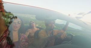 Front view of young multi-ethnic friends driving in red convertible. Car at sunset stock footage