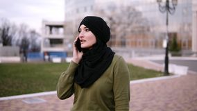 Front view of a young muslim woman in a traditional headscarf and green dress talking with friends on a smartphone in stock video