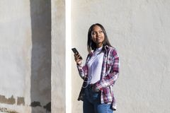 Front view of a young smiling african american woman standing outdoors while smiling and listening music by earphones in a sunny stock image