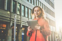 Front view.Young smiling attractive woman in orange coat is standing on city street and uses tablet computer. Royalty Free Stock Photos
