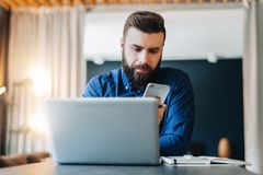 Young smiling bearded businessman sitting at table in front of computer, using smartphone. Freelancer works at home. stock images
