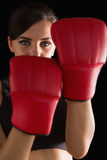 Front view of young sporty woman posing wearing boxing gloves Royalty Free Stock Photos