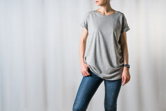 Front view of young woman, dressed in a gray T-shirt and blue jeans, standing on light gray background Royalty Free Stock Image