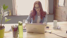 Front view of young woman freelancer smiling and working on computer. stock video