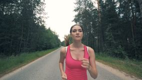 Front view of a young woman while running in slow motion stock video footage