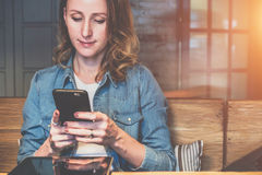 Front view of young woman sitting in cafe at table and use smartphone.On table is tablet computer. stock photography