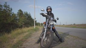 Front view of the confident young woman in leather dress sitting on her bike at the road. Hobby, traveling and active. Front view of the young woman sitting on stock video