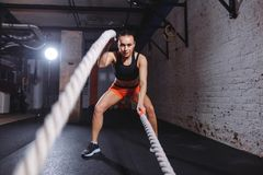 Young woman working out with battle ropes in cross fit gym. Front view of Young woman working out with battle ropes in cross fit gym Royalty Free Stock Photo