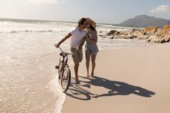 Young woman kissing on man cheek at beach. Front view of young women kissing on men cheek at beach in the sunshine royalty free stock photos