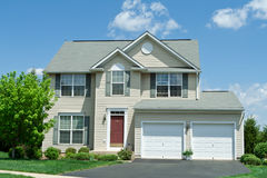 Front Vinyl Siding Single Family House Home MD. Modern vinyl sided single family home in suburban Maryland.  House has two car garage, driveway and red door Stock Photos