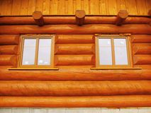 Front wall detail with windows built in wooden beams cabin wall. Painted wood with fungicide light red paint. Detail of window built in wooden beams cabin wall stock photos