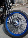 Front Wheel with Blue Rims and Fat Chrome Spokes of Vintage Styl. E Motorycle; cylinder head and other gear is also partly visible Stock Photography