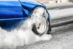 Front wheel drive drag racing car at start line. Front wheel drive drag racing car burning tire at start line Royalty Free Stock Image