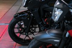 Front wheel of modern black motorcycle on concrete and metal ground stock photos